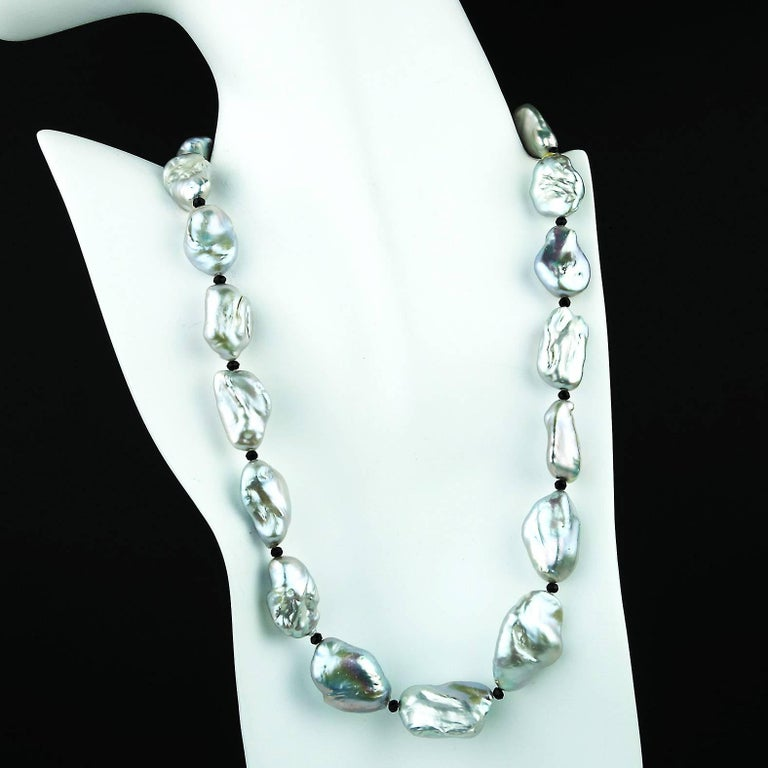 Glowing, iridescence is the major feature of this custom made Baroque Pearl necklace.  The silvery tone is enhanced by flashes of pink, green, purple, and blue.  The Baroque Pearls are gently graduated in size from 21x14MM to 28x19MM. The Pearls are