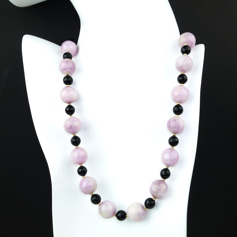 Highly polished 14 MM opaque Kunzite is combined with faceted sparkling Black Onyx, 8MM in this stunning, custom made necklace.  Gold tone accents set off these gem quality Kunzites and Black Onyx.  This unique 18 in necklace is secured with a gold