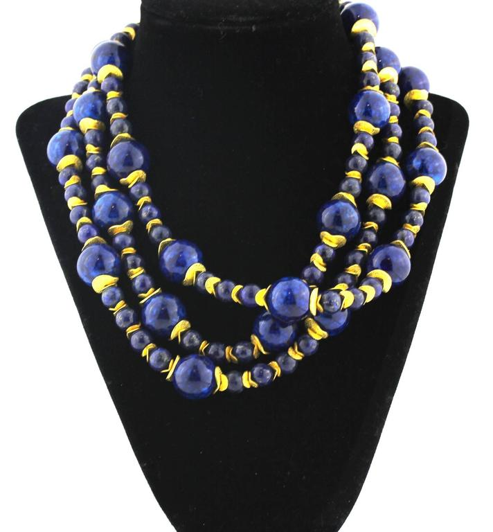 Triple strand of natural Lapis Lazuli from Afghanistan mixed with Blue Coral nicely polished to show off its goldy color flecks with light goldy tone accents necklace Size:  Large Lapis approximately 16 mm Length:  17 inches Clasp:  gold tone