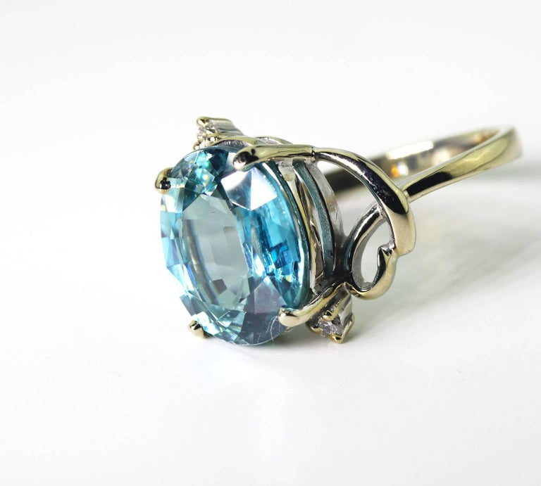 Set in a unique handmade 14Kt white gold ring enhanced with two tiny diamonds this beautiful glistening translucent blue Zircon is 7.8 carats of glittering beauty.  the ring is a size 7 (sizable)  More from this seller by putting gemjunky into