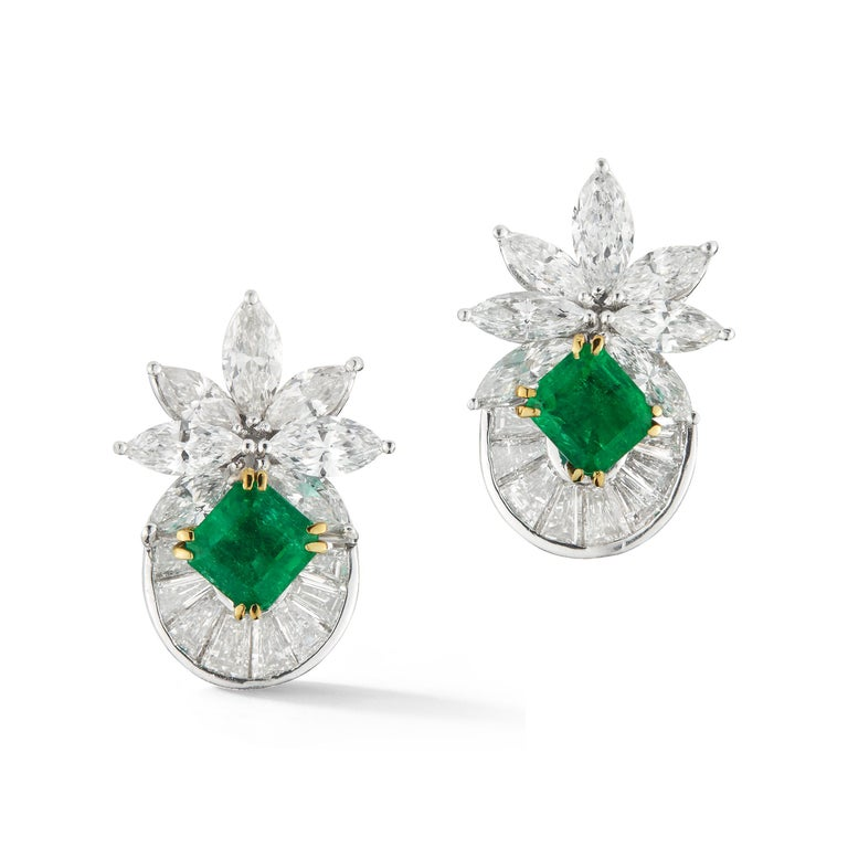 Elegant Diamond and Emerald Earrings, Set with 5 carat of Marquis shaped Diamond plus 5 carat of Baguettes shaped Diamonds. in the center the Earrings are set with two Emeralds.