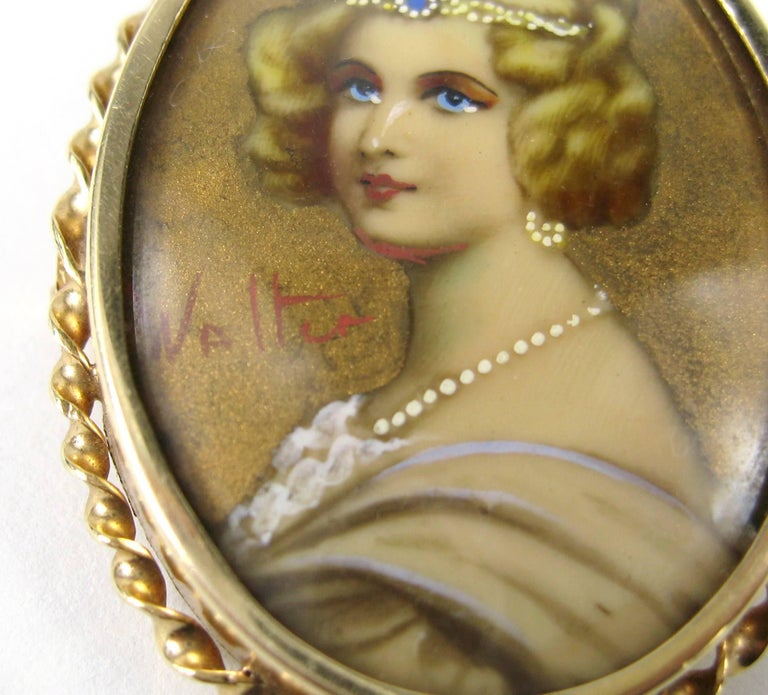 14k yellow gold antique  hand painted on porcelain portrait brooch pin with bale on the  back.  The portrait is under glass depicting a stylish dressed woman. Signed  Measuring 1.75 inches or 44.49mm x 1.35 inches or 34.4 mm  Any questions please