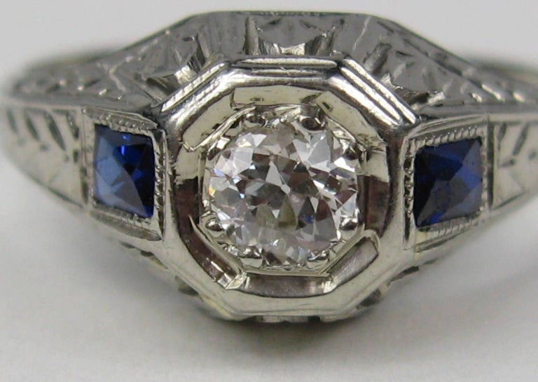 Lovely example of the impeccable Art Deco designs of the 1920's. Set in 14K White Gold - Center Diamond, Clarity VS, Color H/I, Carat 1/4. Size is a 6 and can be sized by our jeweler or yours. Please be sure to check our storefront for more jewelry