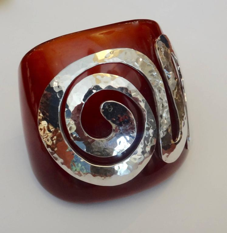 This amber colored vintage bakelite cuff is embellished with a spiral of forged sterling silver.  The silver has been rhodium plated to prevent tarnishing.  6 inch inside circumference.