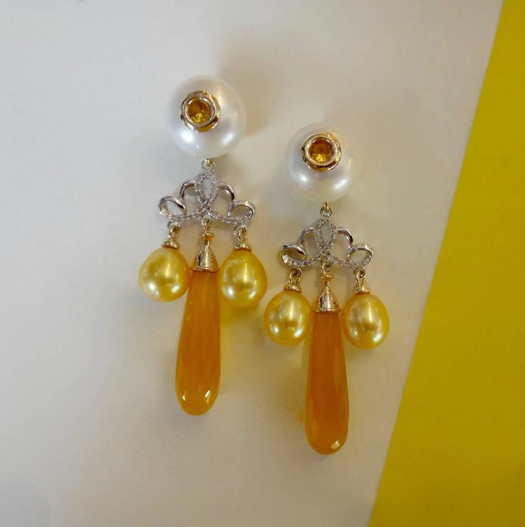 Golden chalcedony briolette in a rich yellow/orange color dangle from white button pearls that are drilled and set with bezeled yellow sapphires.  Gold drop shaped pearls further decorate these two tone, micro-pave diamond dangle earrings.  Post