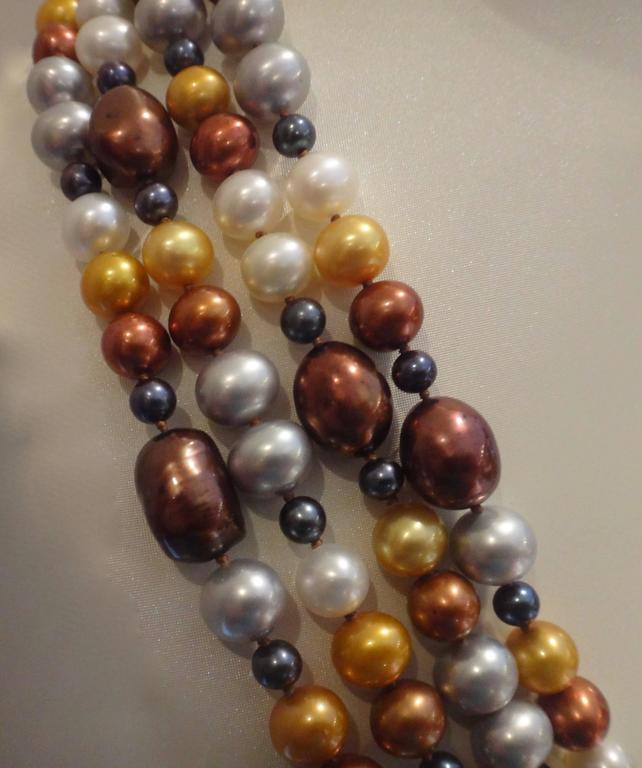 A collection of pearls in shades of bronze, copper, gold, yellow, white and black are knotted together into this dramatic four strand necklace.  Yellow gold slide clasp.