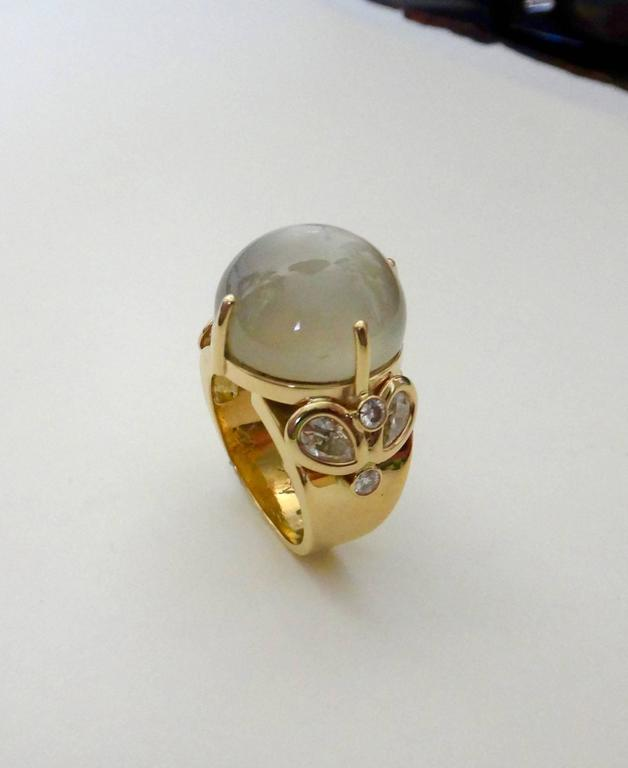 A highly domed cabochon moonstone of exceptional clarity is featured in this one-of-a-kind cocktail ring.  The center stone is flanked by a cluster of pear shaped and brilliant cut diamonds.  The handmade setting is 18k yellow gold.  The ring is a