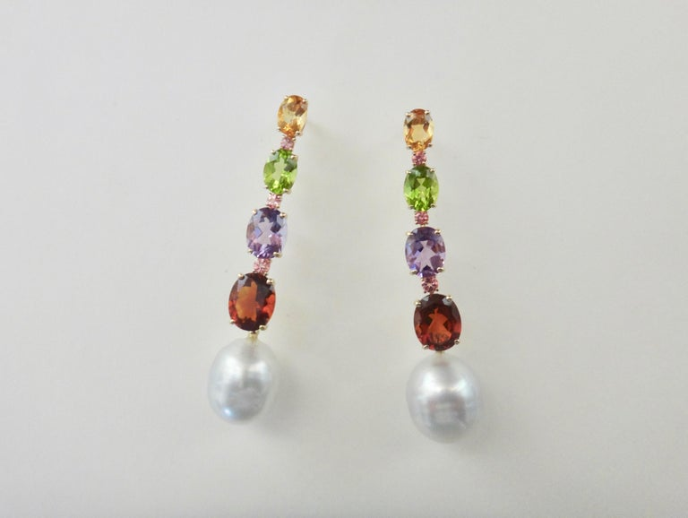 Citrine, peridot, amethyst and garnet are oval cut, graduated in size and spaced with round pink tourmalines in these delightful dangle earrings.  Completing the dangles are a pair of baroque, gem quality Paspaley South Seas pearls.  The mountings