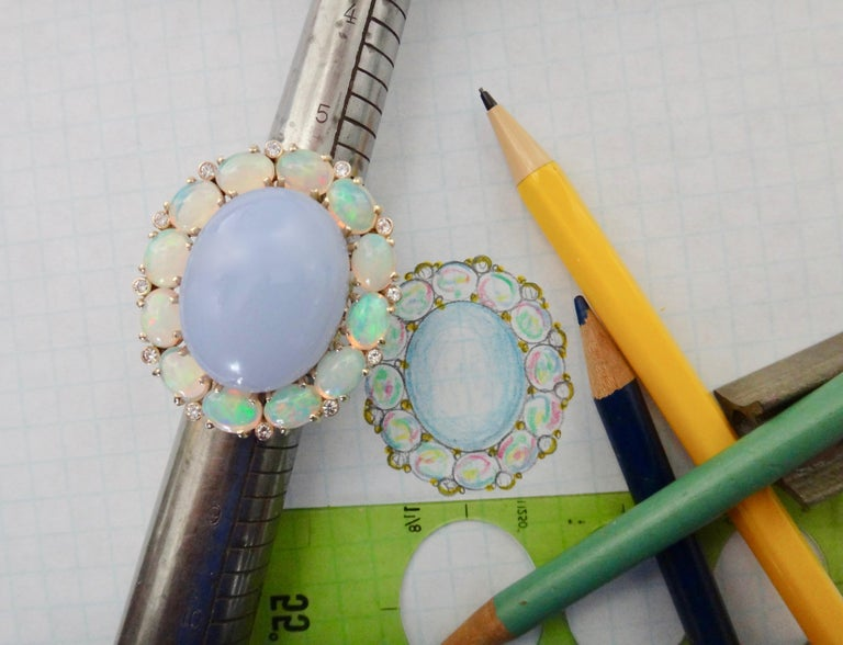 A delicately colored blue chalcedony with a delicious polish is the centerpiece of this dinner ring.  The cabochon is surrounded by 12 Ethiopian opals with a full range of colors including blue, green, pink and orange.  Spaced between the oval