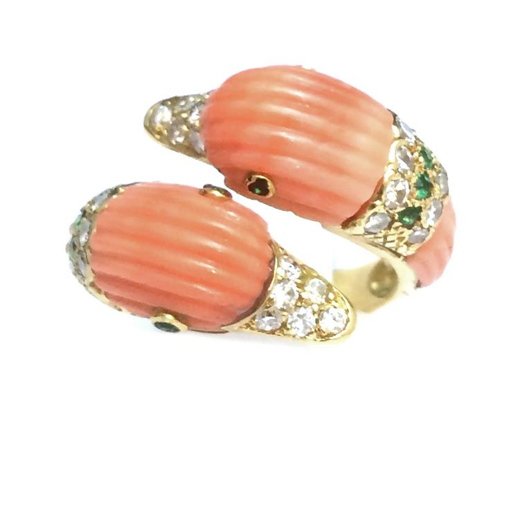 """A magnificent """"You and Me"""" Van Cleef & Arpels ring in 750/000 yellow gold designed as two ducks embellished with pink coral highlighted with circular-cut emeralds and brilliant cut diamonds. The eyes are set with circular-cut emeralds, and the beak"""