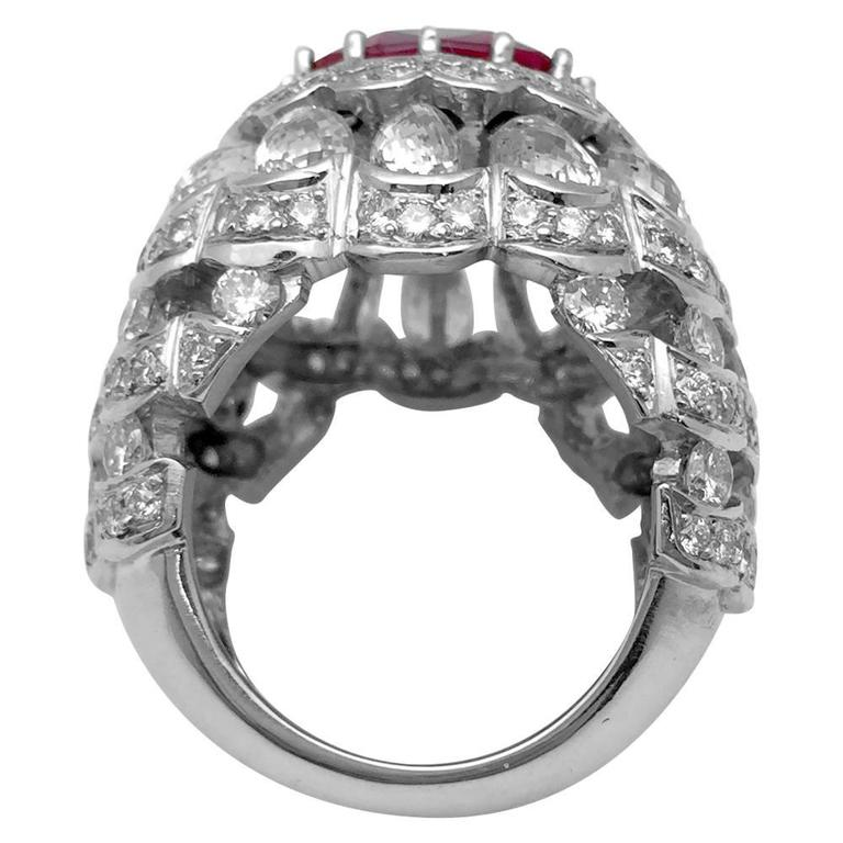 A 750/000 white gold dome-shaped ring set in the middle with an oval-shaped ruby surrounding by brilliant cut diamonds.  The mounting is enhanced with briolette-cut diamonds and with lines of brilliant cut diamonds.  Ruby's weight : 5,04