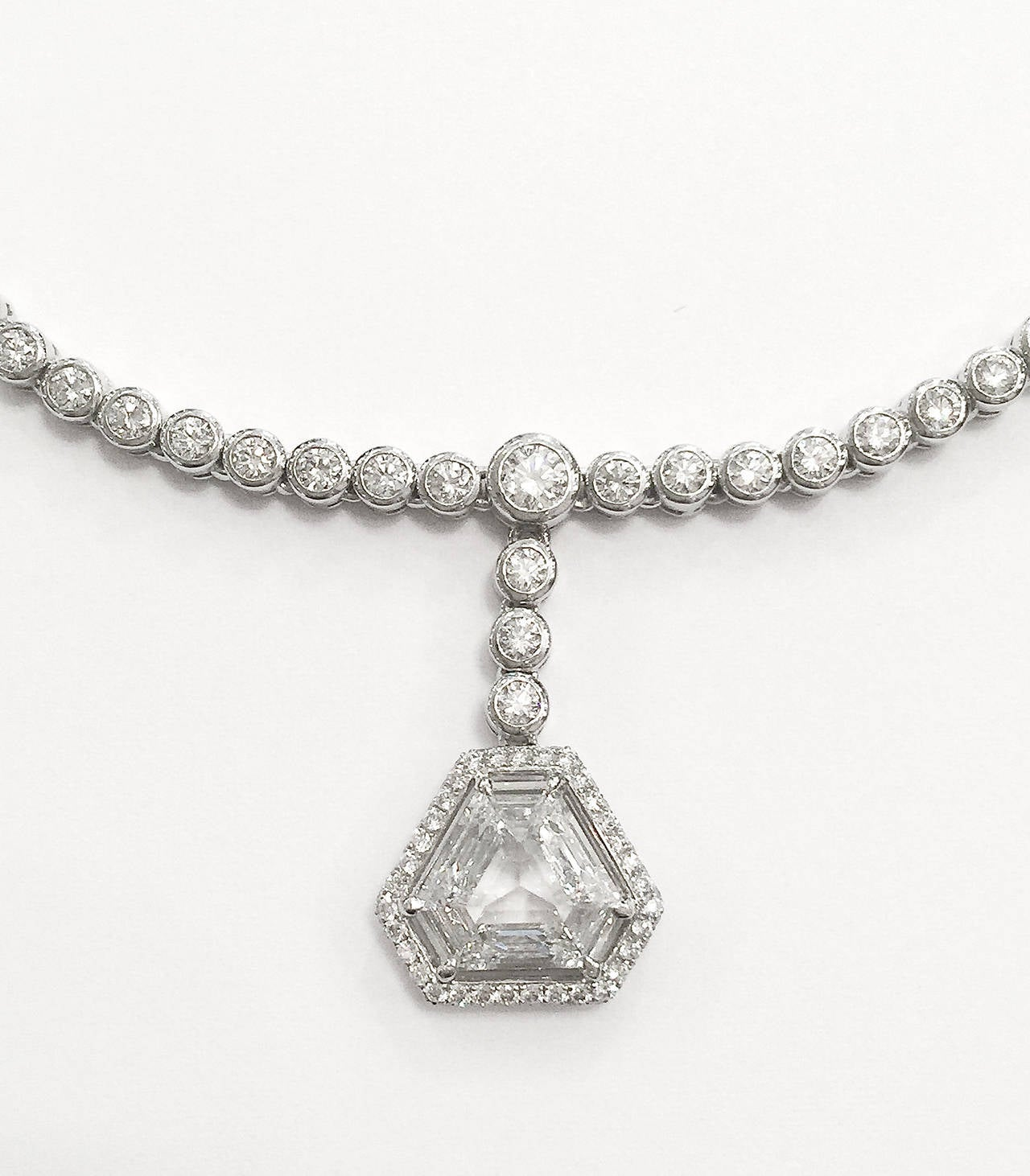 A white gold necklace entirely set with 5,14 carats of brilliant-cut diamonds and a triangular diamond of 1,60 carat surrounded with 77 brilliants for 0,34 carat.