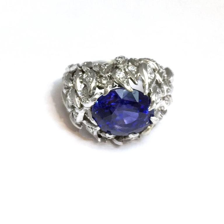 Dome platinum ring set with a 9 carat natural burmese sapphire surrounded with brilliants in a pattern of flames. Weight : 32,10 grams. Two certificates stating the estimated weight of the stone is 9 carats and natural saphir from Myanmar