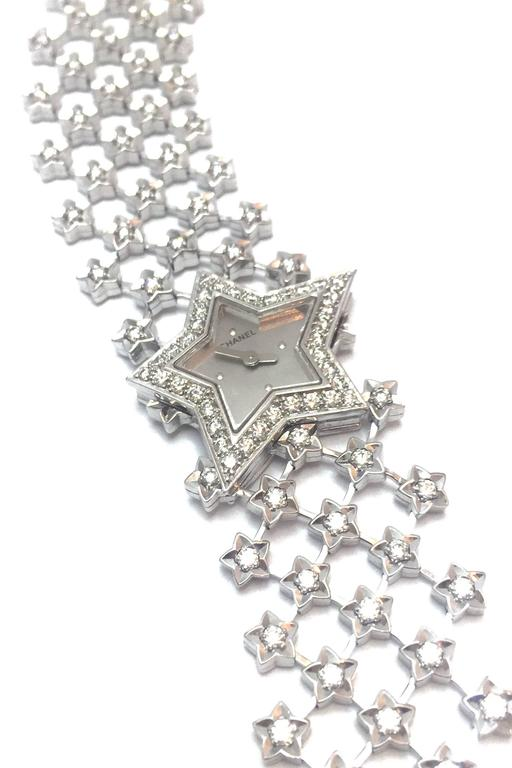 """A 750/000 white gold jewelry Chanel watch, """"Poussière d'étoile"""" collection.  The bezel in shape of a star is set with diamonds, the large crossed motif bracelet is enhanced with falling stars, silvered dial.  Circa 2000. Quartz"""