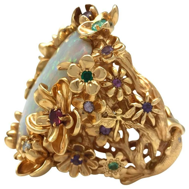 Exceptional yellow gold Dior cocktail ring centered with an important white opal, the ring is enhanced with floral, fish, dragonfly and a frog motifs, some of the flowers are centered with quartz, tourmalines, garnets, sapphires or diamonds. Length