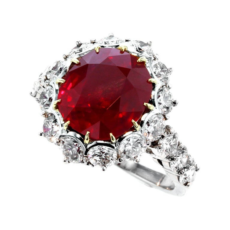 A beautiful and stunning ring centered with a five carat ruby from the coveted mines of Burma (Myanmar) surrounded with eighteen round brilliant-cut diamonds, along with a diamond encrusted 'G'; stamped GARRARD, and PT900, ring size 5 3/4 US.  The