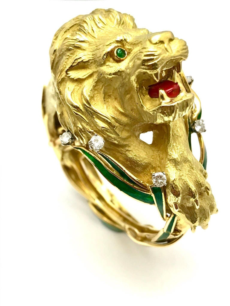 A round brilliant diamond and green and red enamel 18 karat yellow gold lion bangle bracelet.  The bracelet is designed as the lion sitting in the in the green enameled grass, letting out a mighty roar, exposing his red enameled tongue.  The lion is