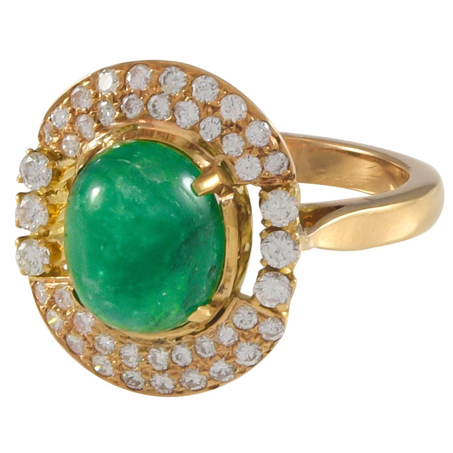 A beautiful 2.70ct rich green, cabochon cut emerald and diamond ring set in 18k yellow gold.  The surrounding diamonds are round brilliant cut with an estimated total weight of .50cts.