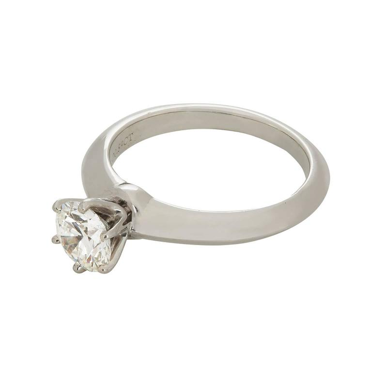 A stunning Tiffany & Co. round brilliant diamond solitaire platinum ring.  the diamond is set in a six prong head on a knife edge shank.  The diamond is 0.89cts, E color, VS1 clarity.    Signature:  Tiffany & Co. Hallmark: