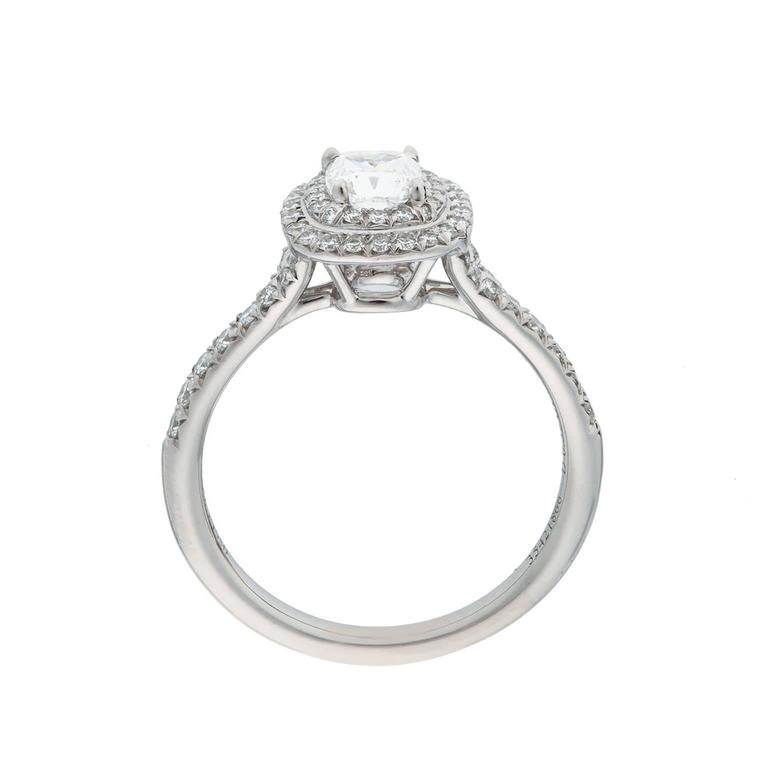 A beautiful Tiffany & Co. cushion shape diamond platinum ring.  The center diamond is 0.52cts, H color, VS1.  It is set atop a double halo of round brilliant diamonds, with a split diamond half shank, with an estimated total weight of