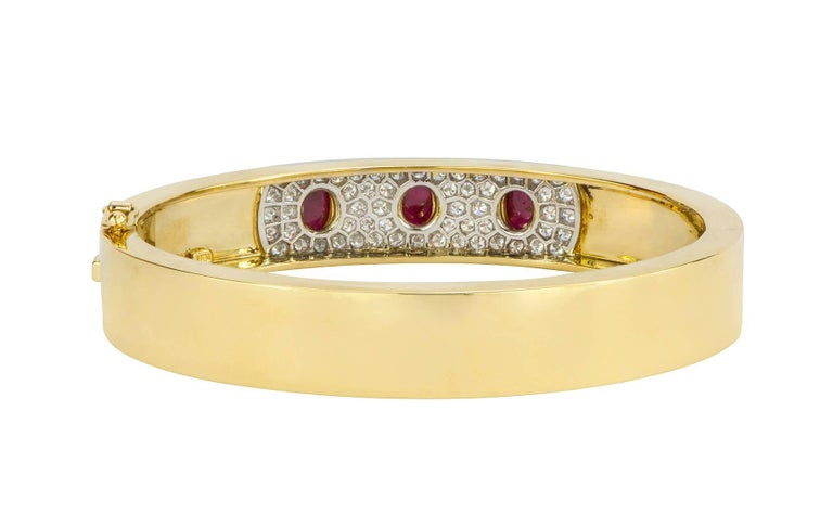 A hinged bangle bracelet made up of three cabochon rubies bezel set in a pave diamond station of platinum in the center of the 18k yellow gold bangle.  The three rubies have an estimated total weight of 2.30cts, with 0.82cts in diamonds.  The