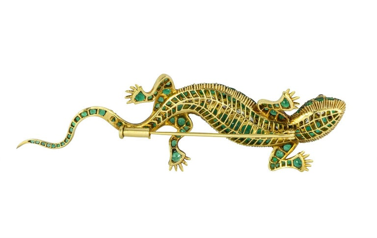 Emerald and diamond 18k yellow gold lizard brooch with ruby eyes.  The lizard contains an estimated 6.26cts in round cut emeralds, with an estimated 2.10cts in round brilliant diamonds.  The ruby eyes are approximately .10cts total.  The color of