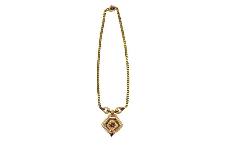18kt yellow gold ruby and diamond necklace.  The necklace contains 7.26cts in rubies, and 3.01cts in diamonds.  Designed with a tiered pendant containing a  cabochon ruby center, surrounded by pave round brilliant diamonds, framed by square cut