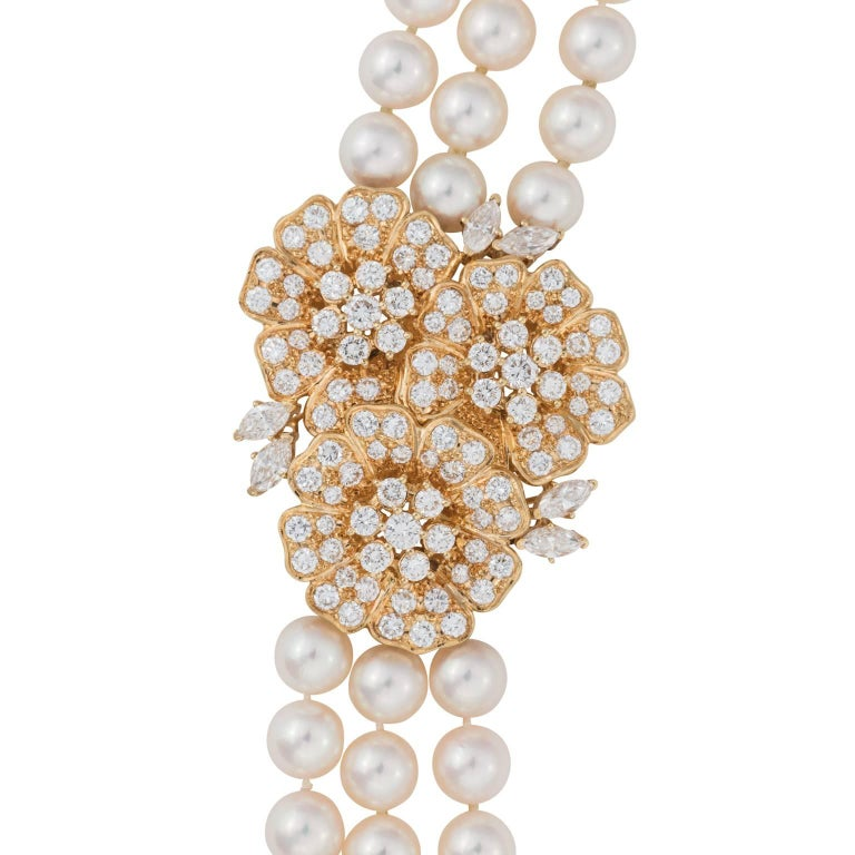 Mikimoto three strand nesting pearls with a diamond and 18k yellow gold clasp.  There are 285 cultured pearls, measuring 7.00-7.50 millimeters.  The clasp is made up of three connecting flowers, containing a mix of round brilliant and marquise