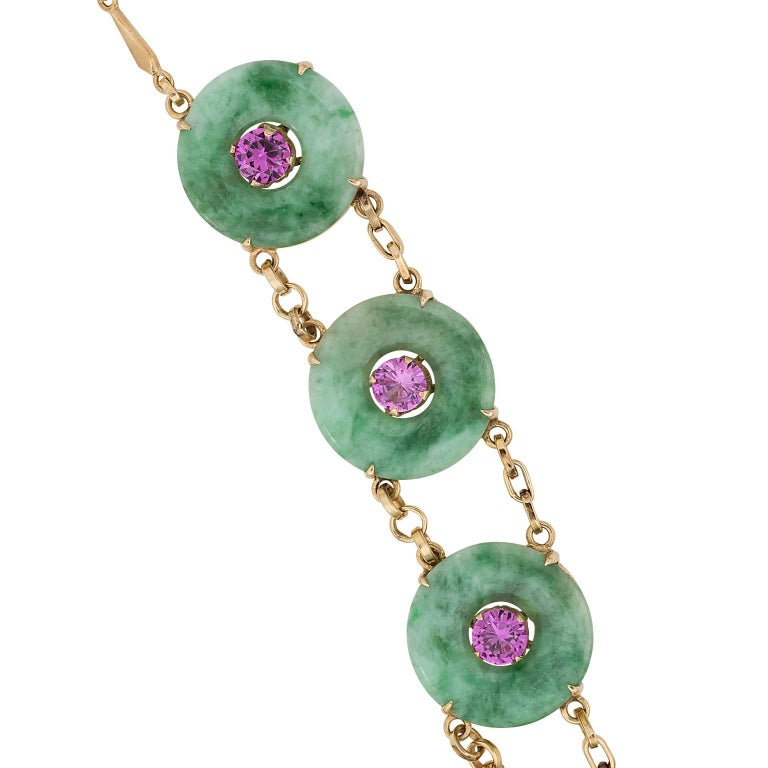 Jade and pink tourmaline 22 karat gold necklace.  The necklace is made up of ten carved jade discs with a round cut pink tourmaline in the center of each.  The discs are linked by a double linked chain.  Length:  18.50 inches