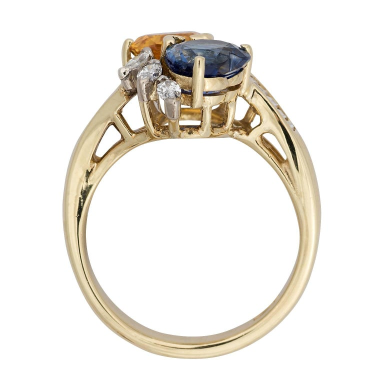 A Hammerman heart shaped orange and blue sapphire and diamond 18k yellow gold ring.  The two sapphires have a total weight of 2.00 carats.  The ring is designed as a bypass with three marquise diamonds on the side of each sapphire, and a channel set