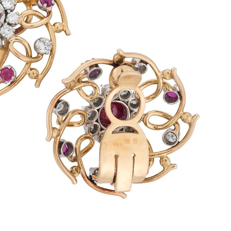 Cabochon ruby and diamond 18 karat yellow gold clip on earrings.  Designed in a pinwheel design, there are ten rubies weighing 1.00 carat total, with 0.64 carats in round brilliant diamonds.    Hallmark:  750 **Posts can be added if needed