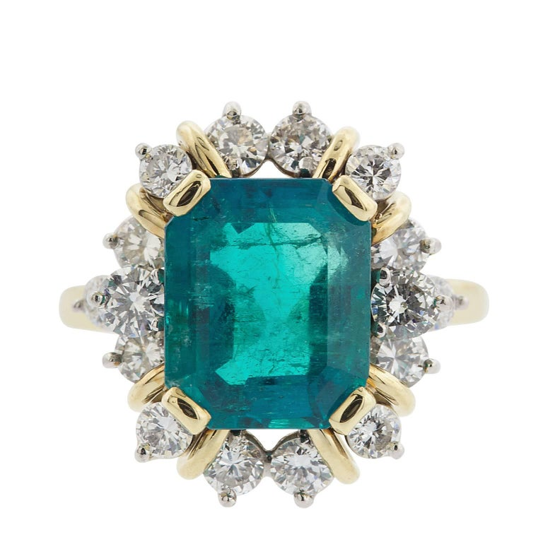 A natural 4.21 carat emerald cut Colombian emerald, surrounded by 1.10 carats in round brilliant diamonds, in 18 karat yellow and white gold.  The emerald has an American Gemological Laboratories Report, stating the origin, and other features of