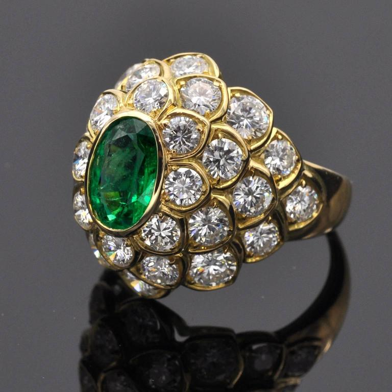 The center of this dome ring is a lively 1,26 carat oval emerald. Around it 30 top quality diamonds are set in a scale like motive cluster. Diamond weight : approx. 4.25 carats