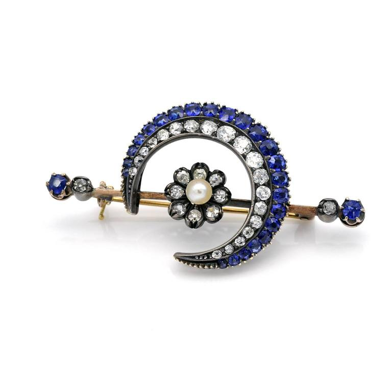 A spectacular Victorian silver topped gold, diamond and sapphire Crescent brooch . In the center of  the crescent a diamond and pearl flower stands.