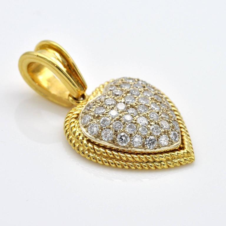 A domed white gold heart richly set with diamonds circled with braided yellow gold.