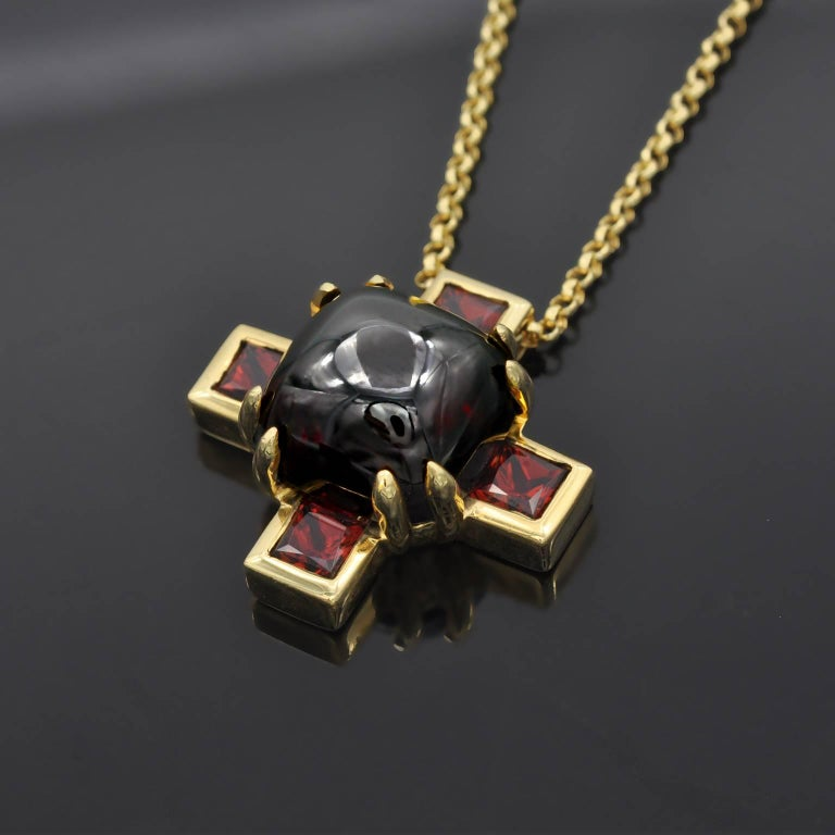 Very fashionnable, modern looking pendant necklace. A nice chubby cabochon garnet in it center, while four princess cut garnets makes the branches of the cross.
