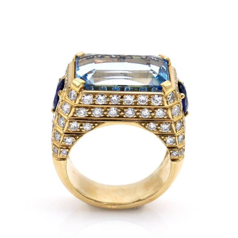 Outstanding one of a kind cocktail ring. A 15 carats emerald cut aquamarine is set on the top of the ring; parallel to its outline diamonds are set in rows. 2 sapphires are set on the shoulders.
