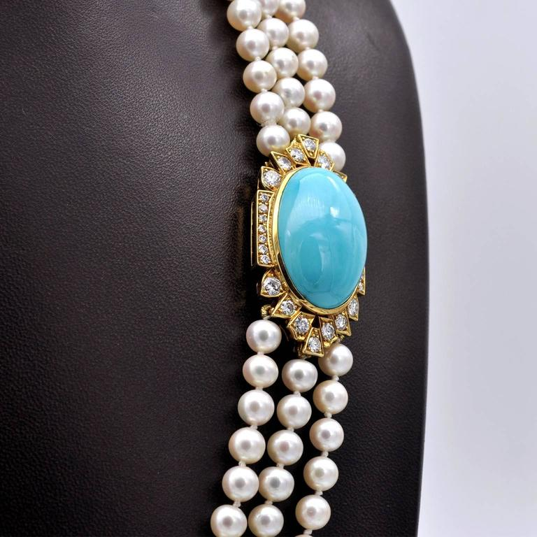 Very elegant opera necklace: thee stands of white peals closing with a yellow gold clasp which is also the adornment of this piece. It consists of a 27mm long turquoise set in yellow gold and surrounded with approximately 2.2 carats of top quality
