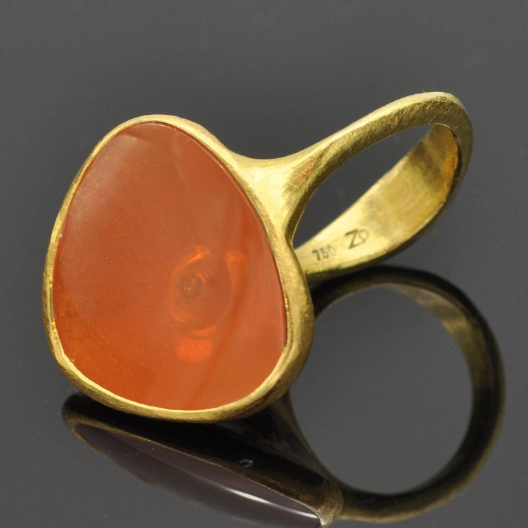 This unique modernist ring seems to get its ethnic inspiration from antique times. A besel set fire opal (16,67 carat ) and beneath it a diamond (0.06 ct) . The ring itself is 18 KT gold.  The opal is nested between two fingers thanks to The sensual