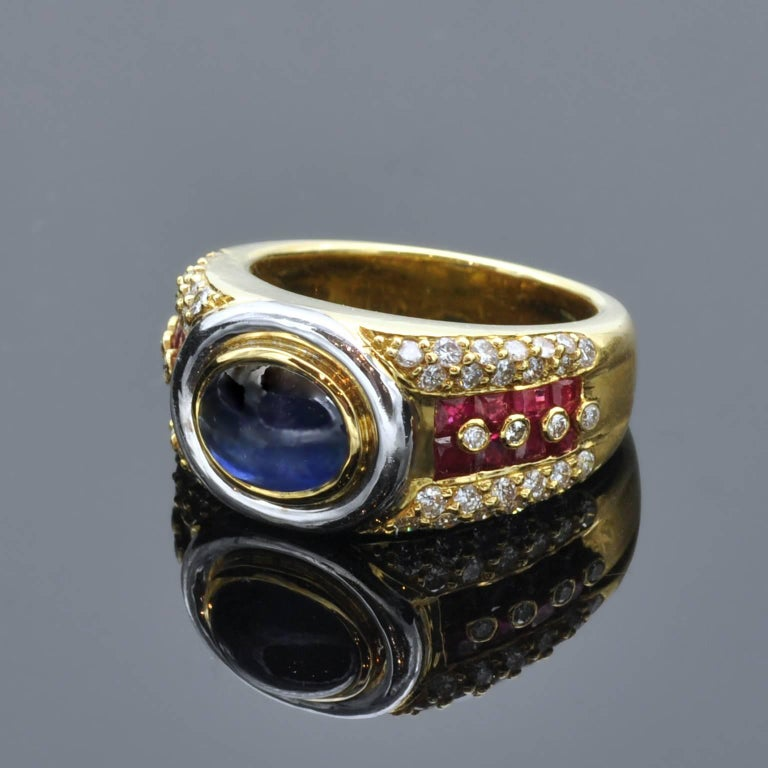 Impressive ring : in it center, a cabochon sapphire circled in white and yellow gold. On the yellow gold body of the ring square rubies and white diamonds.It is a  well made ring and has a nice heavy feel in hand.