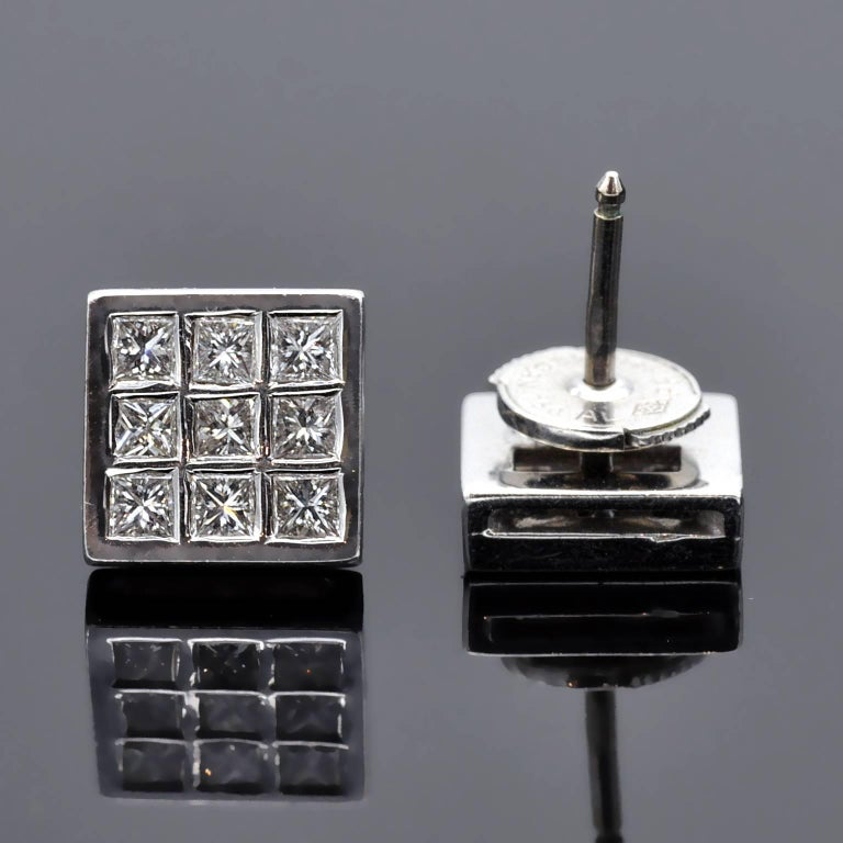 Timeless square studs earrings composed each by nine princess cut diamonds in a grid-like pattern. These diamonds weigh 0.81 carat and are bezel set on 18 kt white gold; they are H in color  VS in clarity.  The Alpa locking system used on these stud