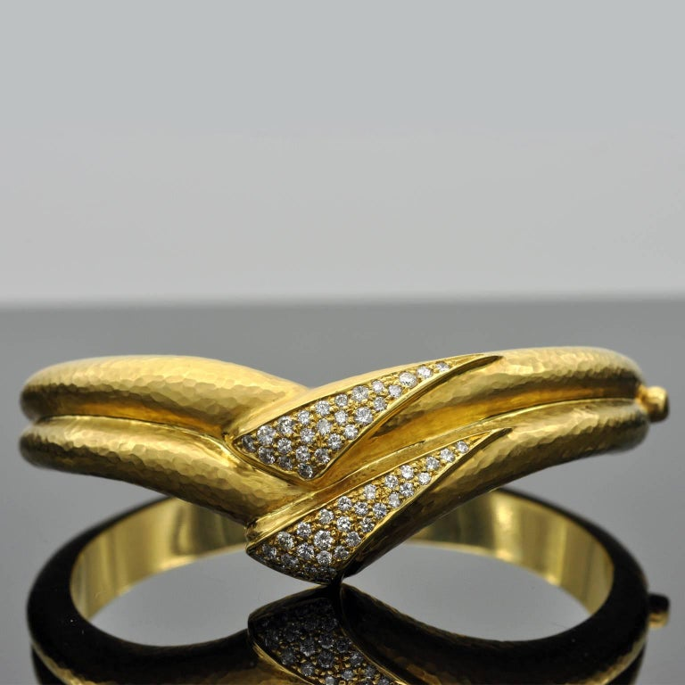 Exclusive cuff bracelet. A double band of 18 kt hand hammered yellow gold form a v-shaped central motif set with round brilliant cut diamonds. It is extremely well made: you can barely see the hinge; It smooth an pleasant in hand and sits perfectly