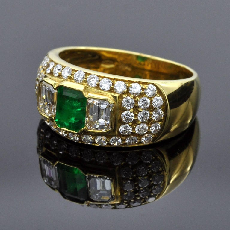 It is a three stone ring in a pave-set band. The center a 0.67 carat emerald is flanked with two emerald cut diamonds . Around this cluster 40 brilliant cut diamond are tightly set giving more light to the whole piece Item details:  Two emerald cut