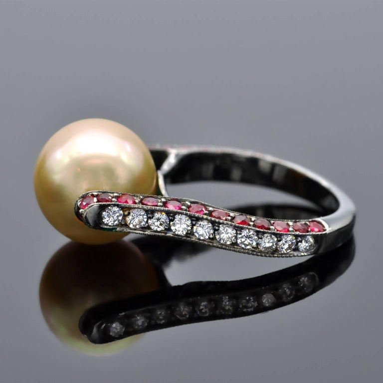 Unique modernist ring. It is a lyra shaped ring in blackened 18 KT gold holding a Golden south-sea pearl. On the shaft round rubies and diamonds are set. Deatails South sea Pearl 11.5-12 mm Rubies: 1.70 carat Diamonds: 0.51 carat