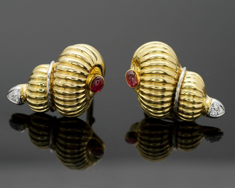 Elegant gem set Gold shell shaped earring and brooch.  The spiral shell itself is 18KT ribbed yellow gold  At the bottom of which  a lively ruby cabochon is bezel set. Each piece is adorned with white gold elements and diamonds.    Details: Rubies: