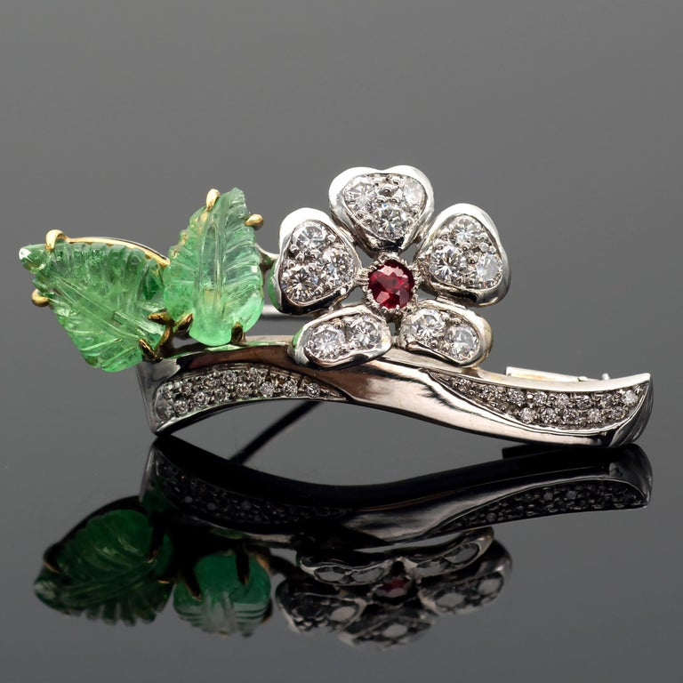 Exquisite floral gemstones and diamond brooch representing two engraved emeralds leaves and a flower on a branch all set in diamonds. The center of the flower is a lively intense red ruby. The make is excellent with a lot of attention to