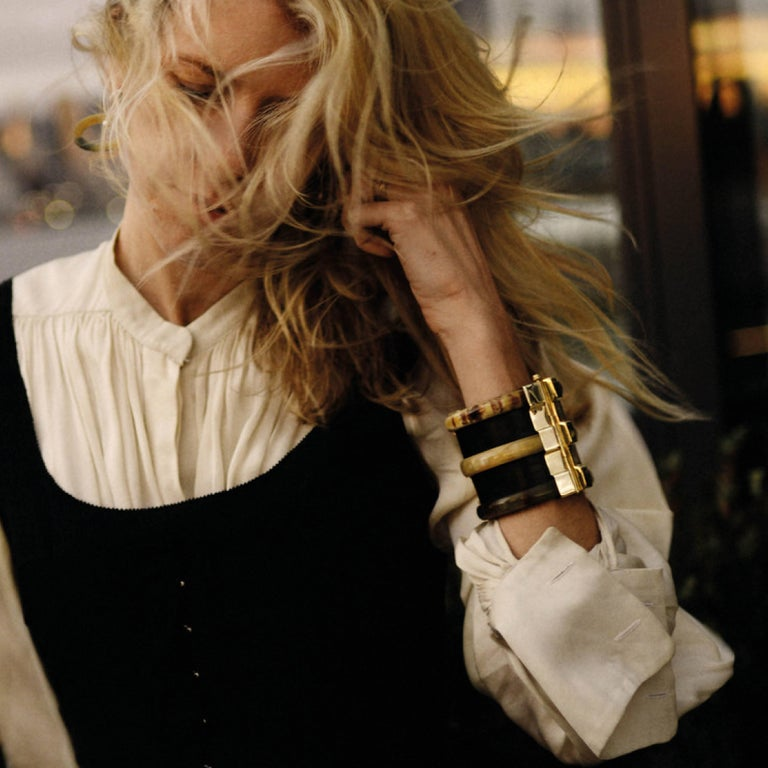 Cuff bracelet hand crafted from ebony wood and African cow horn. The customizable 18k gold plate pin-clasp is set with a choice of blue sapphire, emerald or ruby cabochon. Inspired by warrior style cuffs worn by former Vogue editor Diana Vreeland.