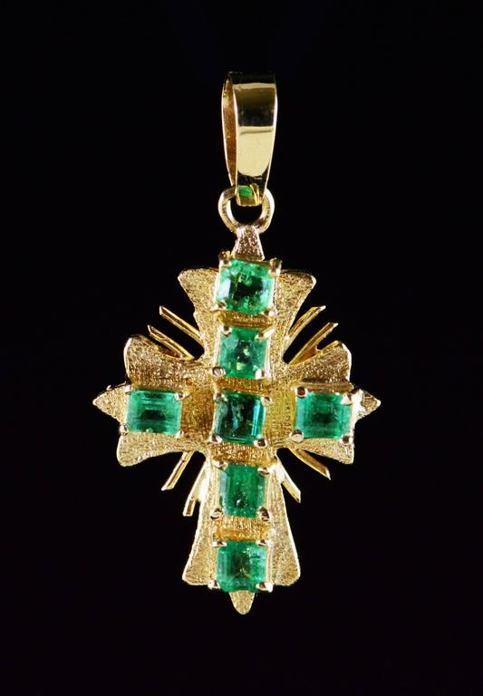 This vintage cross with rays features beautiful emeralds with deep green color saturation.