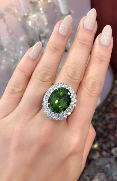 Large Oval Peridot surrounded by two rows of White and Clean Round Brilliant Diamonds in Platinum. The peridot weighs 14.67 carats, with a beautiful deep yellow-green color. It is oval shaped and faceted. The ring has two rows of Round Diamonds. The