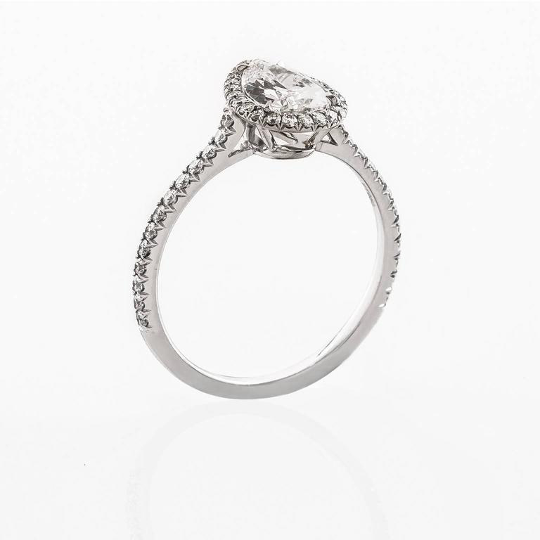 Stunning engagement ring hand fabricated in platinum. Ring centered around a pear shaped diamond embraced by a dazzling halo of french pave set diamonds. The diamond encrusted band gently curves up to meet the center stone.